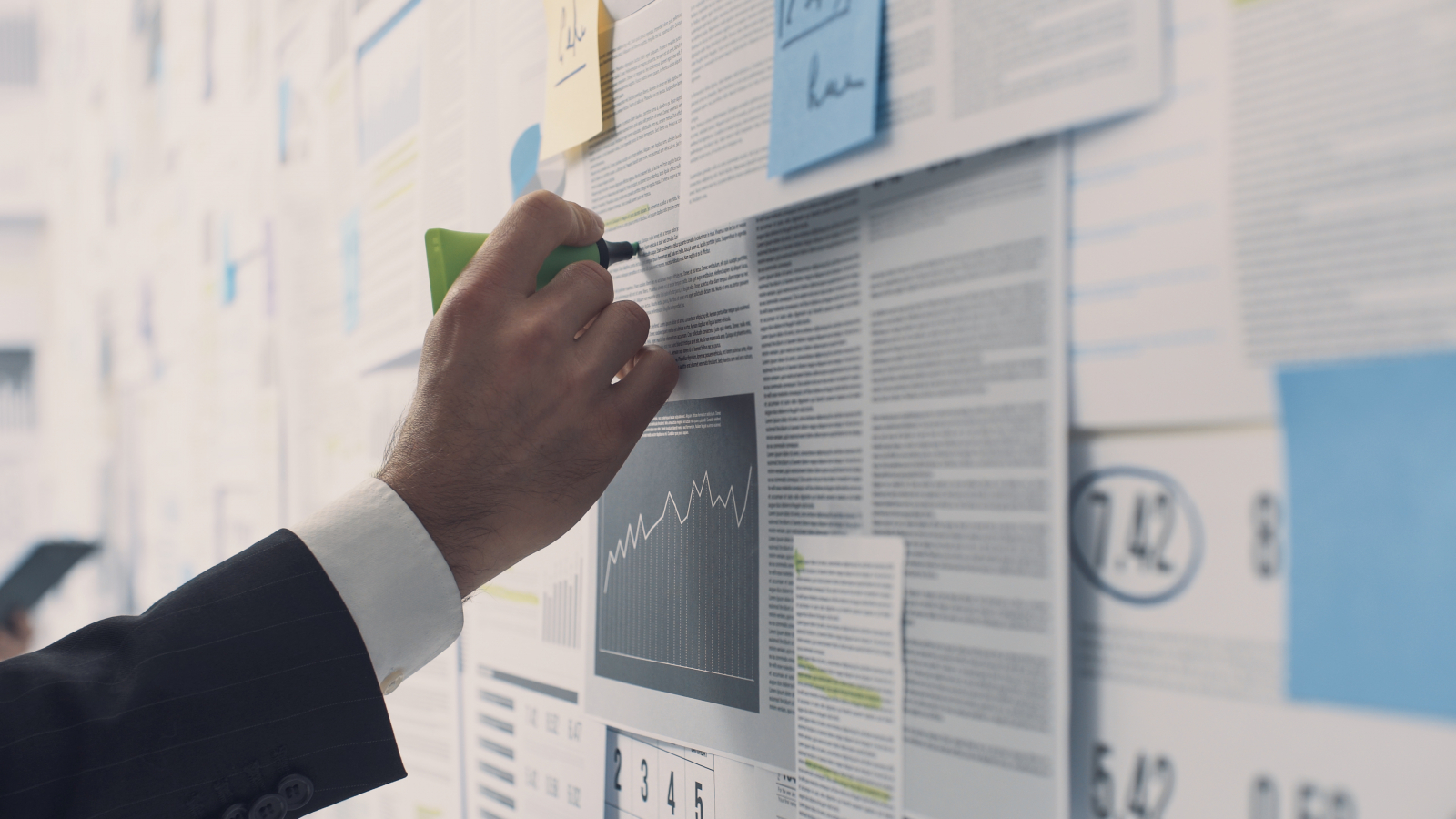 Businessman analyzing a wall with many financial charts and reports, he is underlining text with a marker